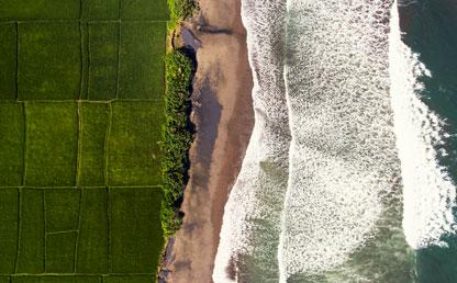 Un prado verde junto a un mar con muchas olas.