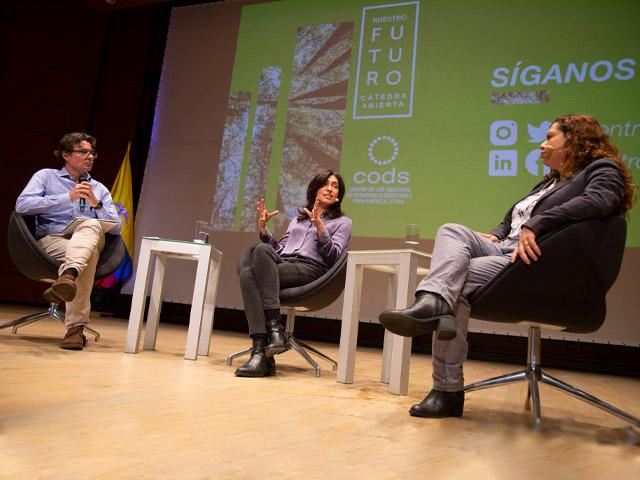 Tres personas sentadas dialogando en un evento.
