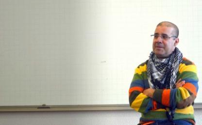 hombre en un salon, ubicado al lado derecho de la imagen con un saco de rayas de colores
