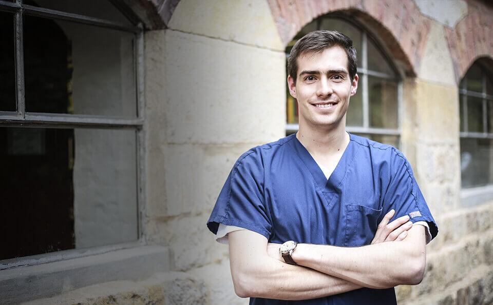 Médico joven parado junto a una ventana, sonríe porque ganó premio