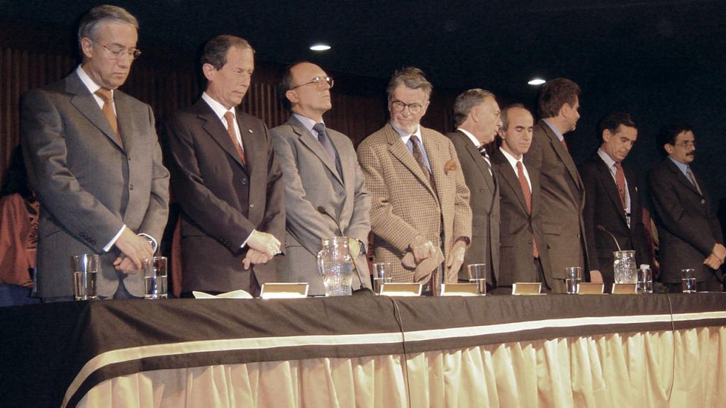 9 personajes en la mesa principal de un evento