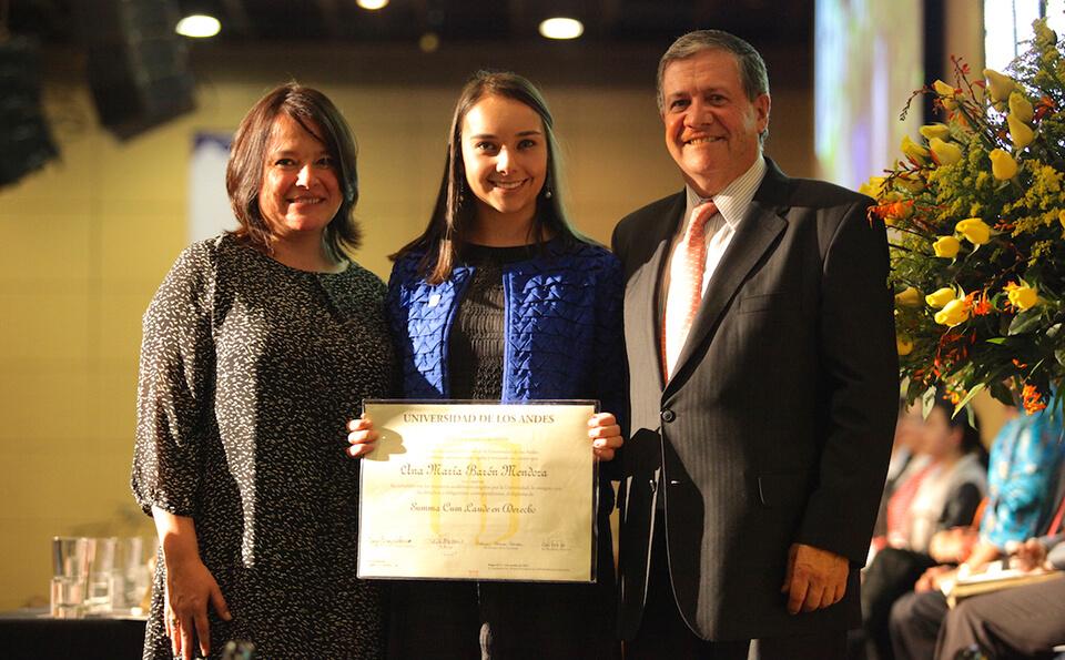 una joven de vestido negro y saco azul muestra su diploma de grado acompañada de un hombre y una mujer