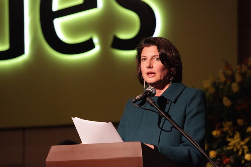 una mujer de abrigo verde oscuro da un discurso frente a un atril