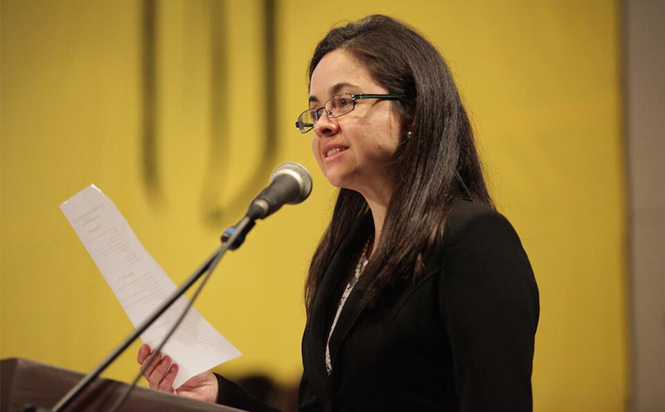 una mujer de cabello largo sostiene una hoja en su mano derecha mientras habla frente a un micrófono, al fondo vemos el logo de uniandes