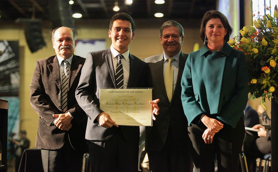 un joven de corbata de rayas muestra su diploma acompañado de dos hombres y una mujer