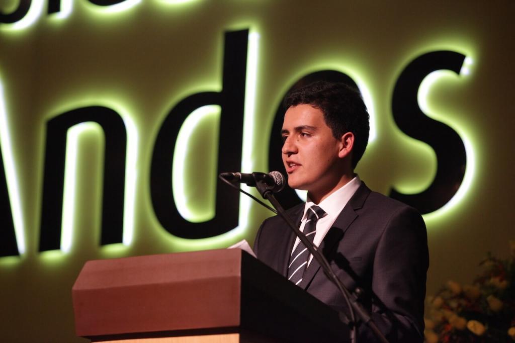 un joven frente a un micrófono se dirige a sus compañeros graduandos