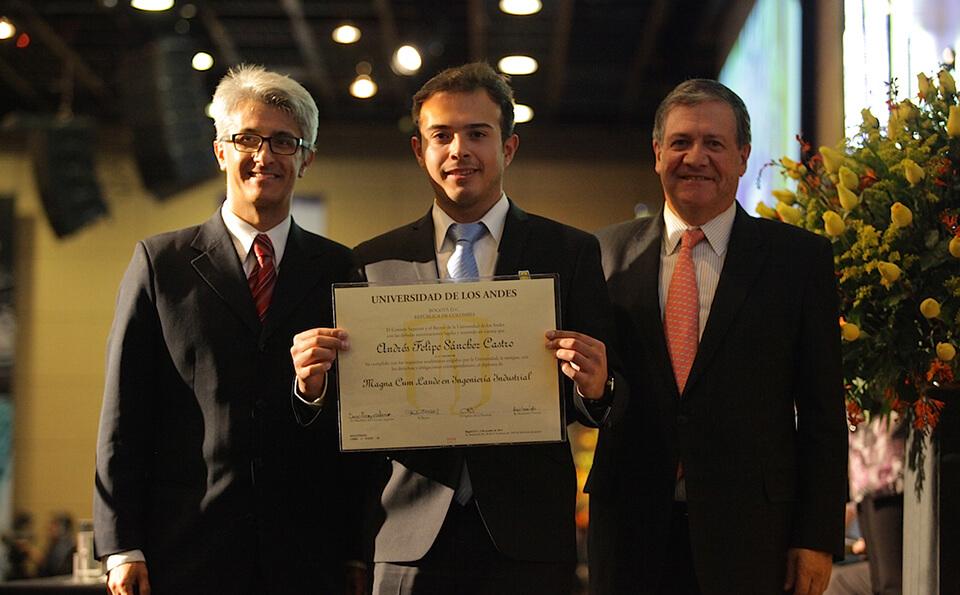 un joven de traje y corbata azul muestra su diploma, acompañado de dos hombres
