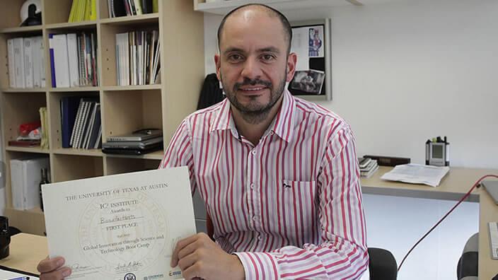 Un hombre con camisa de rayas está sentado en su oficina sosteniendo un diploma en sus manos