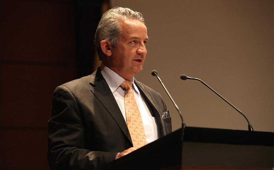 un hombre mayor canoso habla frente a un micrófono dando un discurso