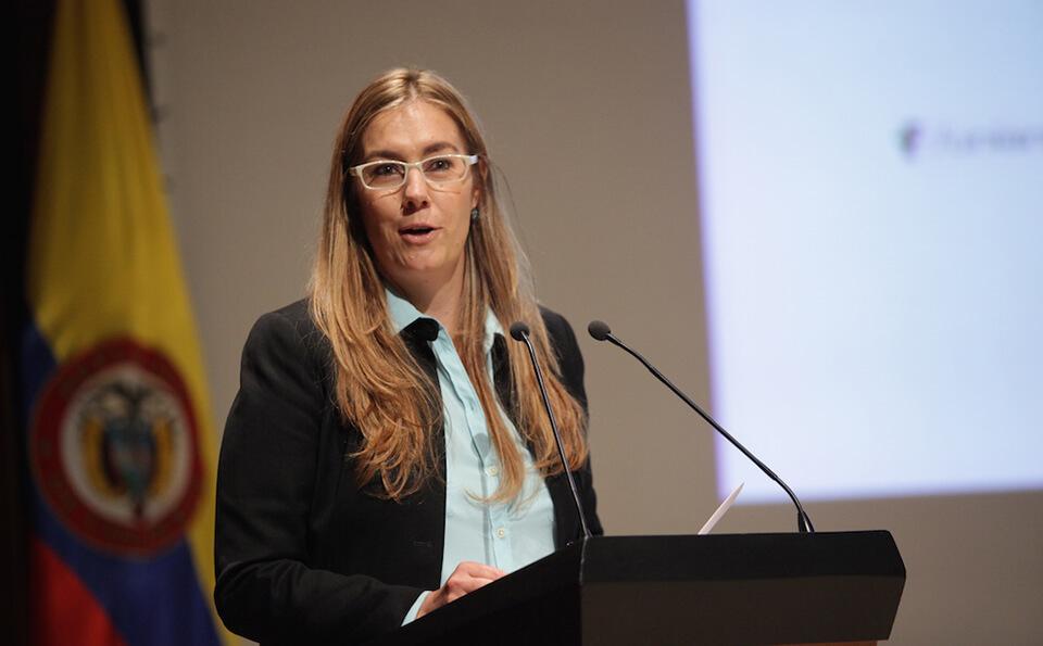 mujer rubia con camisa azul da un discurso en un auditorio