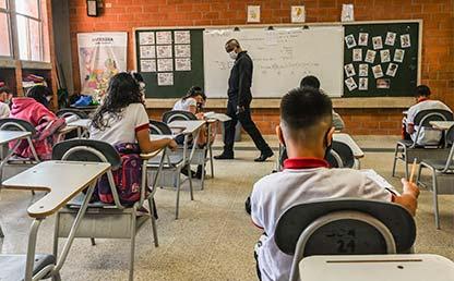 Foto de estudiantes de colegio en un aula de clases durante la pandemia