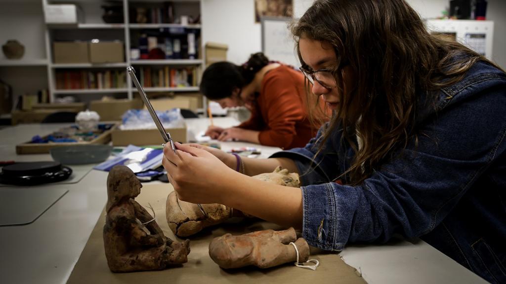 Estudiante manipulando una pieza arqueológica en laboratorio