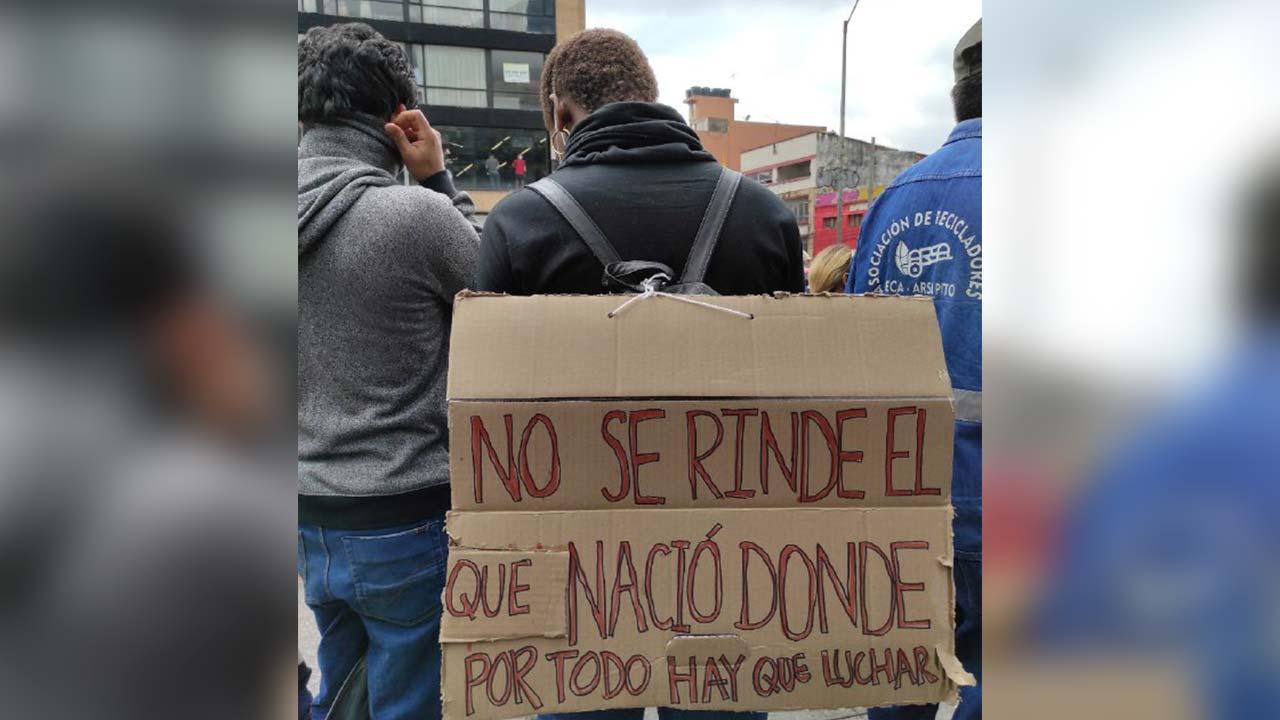 """Foto de un manifestante con el letrero: """"No se rinde el nació donde por todo hay que luchar""""."""