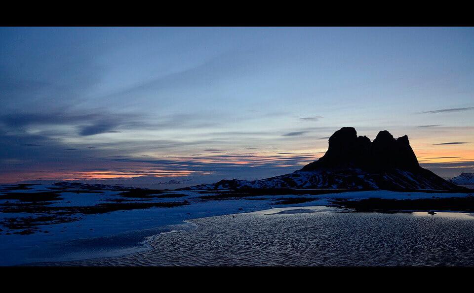 paisaje de atardecer en la antartida, se ven montañas y el cielo despejado