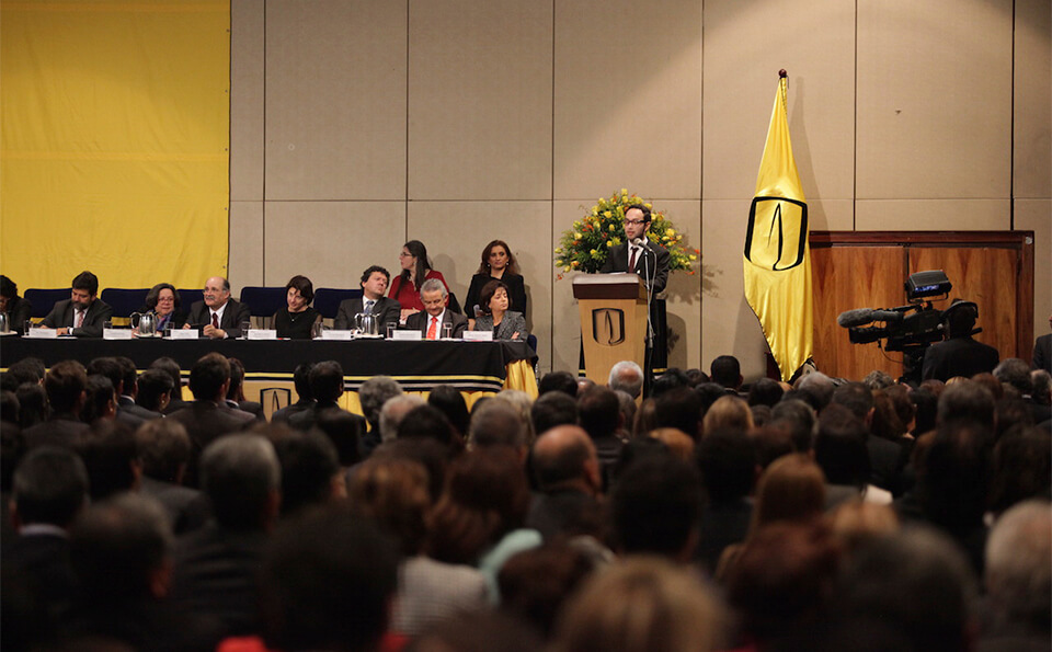 un auditorio lleno de personas en una ceremonia de grados