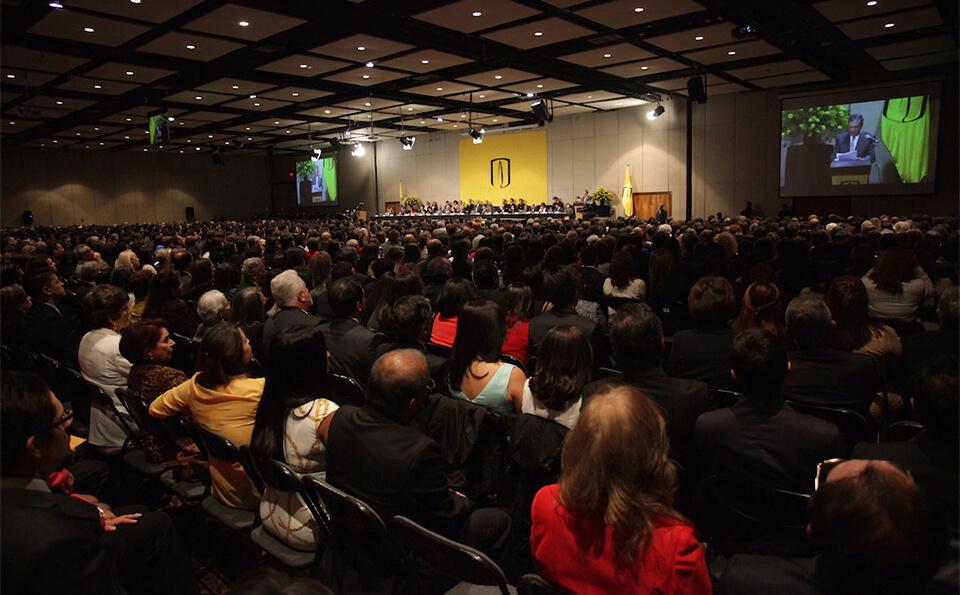 un auditorio visto desde una esquina, se ve lleno de personas sentadas en una ceremonia de grados