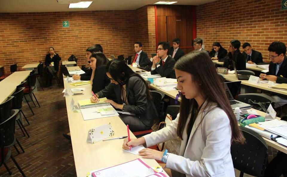 un salón de clases, hay estudiantes vestidos de forma elegante tomando nota