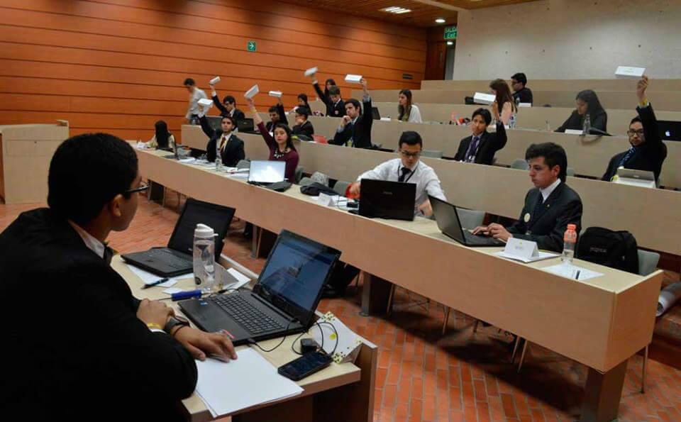salón de clases, se ve a una persona en la parte inferior izquierda de la imagen que está exponiendo un tema