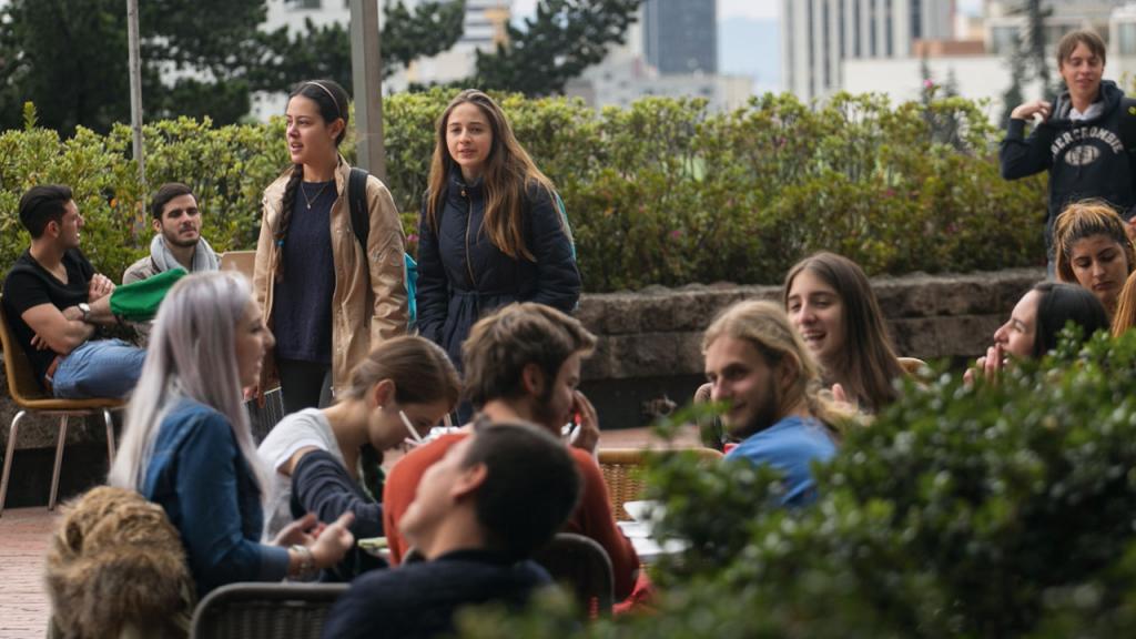 Estudiantes en el campus de la Universidad de los Andes charlan.