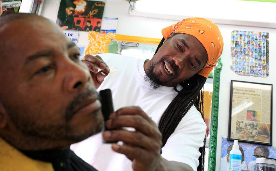 un hombre está afeitando a otro hombre en una barbería