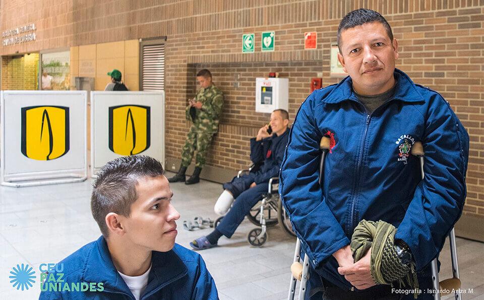 dos hombres con uniforme azul, uno usa muletas, están en evento de donaciones