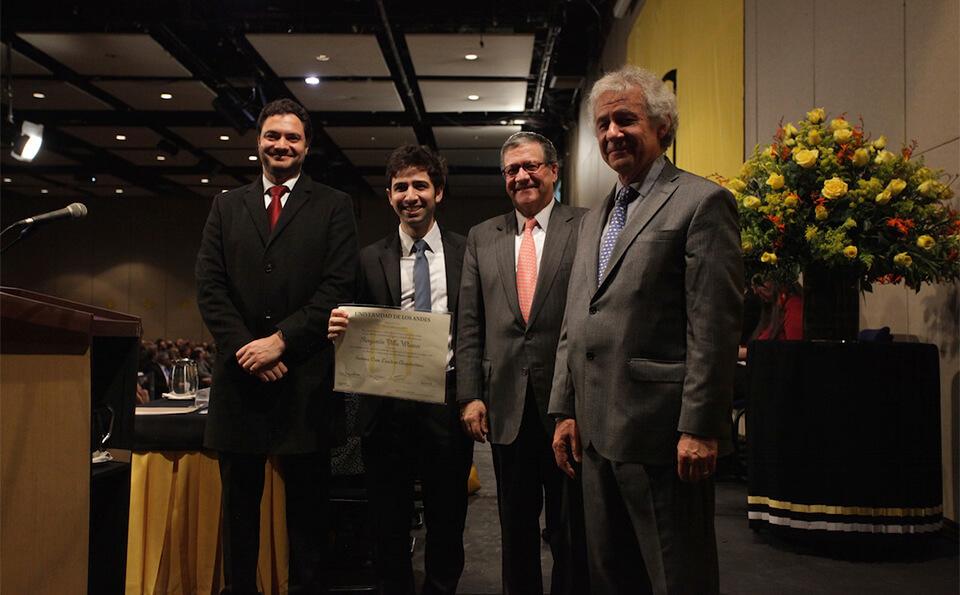 un joven con su diploma en medio de tres hombres directivos y decanos que le hicieron entrega del mismo