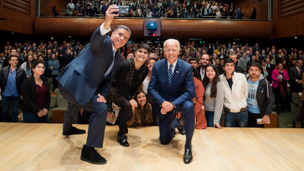 Un hombre se toma una selfie con una estudiante de la Universidad de los Andes y con Joe Biden, vicepresidente de Estados Unidos. De fondo un auditorio lleno de personas.