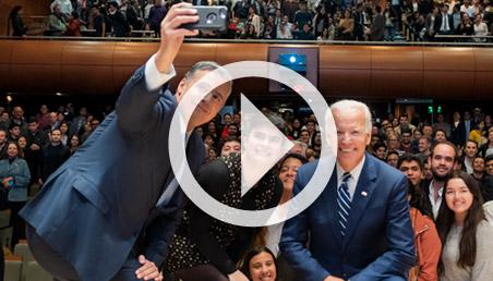 n hombre se toma una selfie con una estudiante de la Universidad de los Andes y con Joe Biden, vicepresidente de Estados Unidos. De fondo un auditorio lleno de personas.