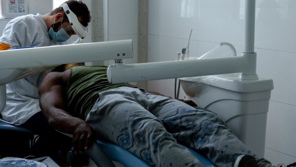 Un odontólogo atiende a un paciente.