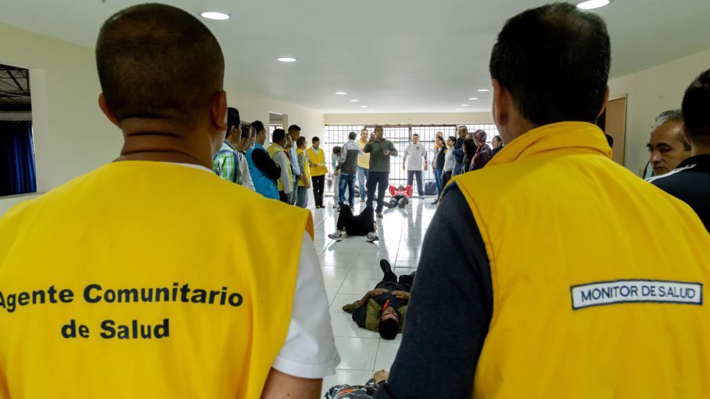 Dos hombres visten chaleco amarillo en el que se lee:  Agente comunitario en salud.