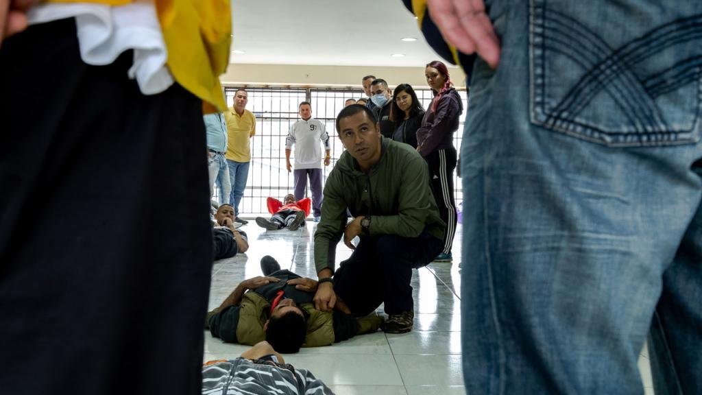 Un hombre arrodillado simula atención en salud  a otra persona