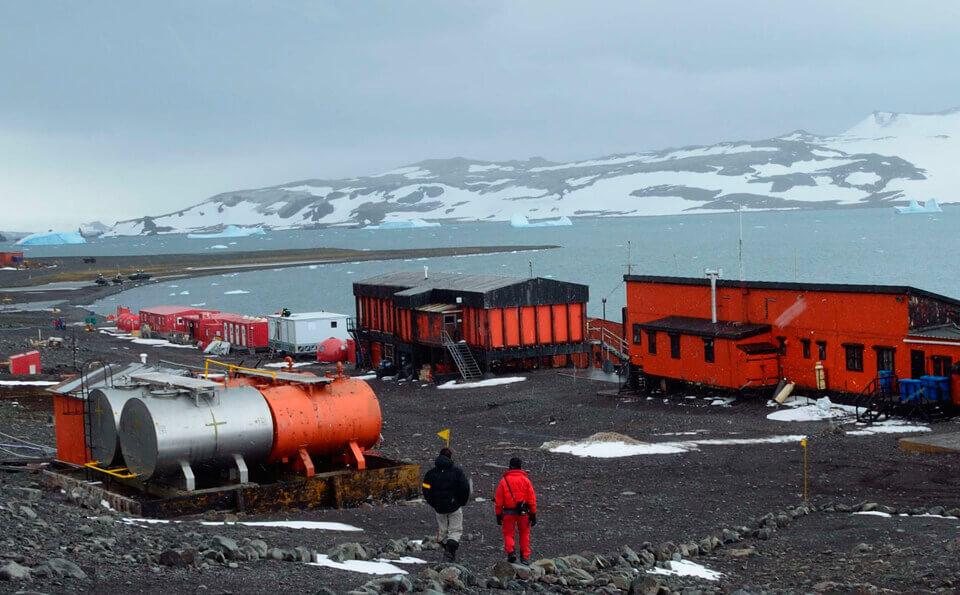 campamento base de investigadores en la antártida, se ven dos personas caminando hacia el