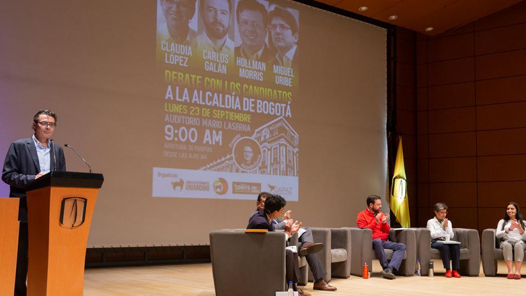 Foto del rector y los candidatos durante el debate