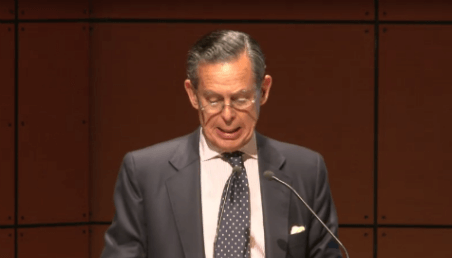 hombre mayor con gafas habla en un auditorio