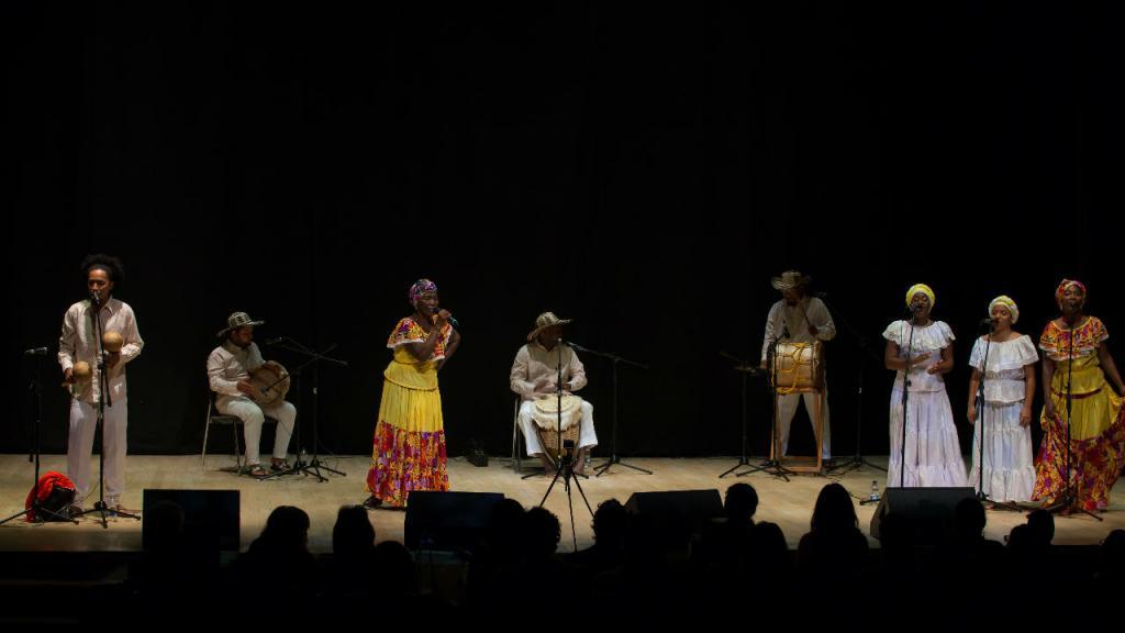 Fotografía de Ceferina Banquez, cantadora de bullerengue en concierto. La acompañan en tarima músicos y bailadores.  Es afrodescendiente, y aparece con un turbante en la cabeza.