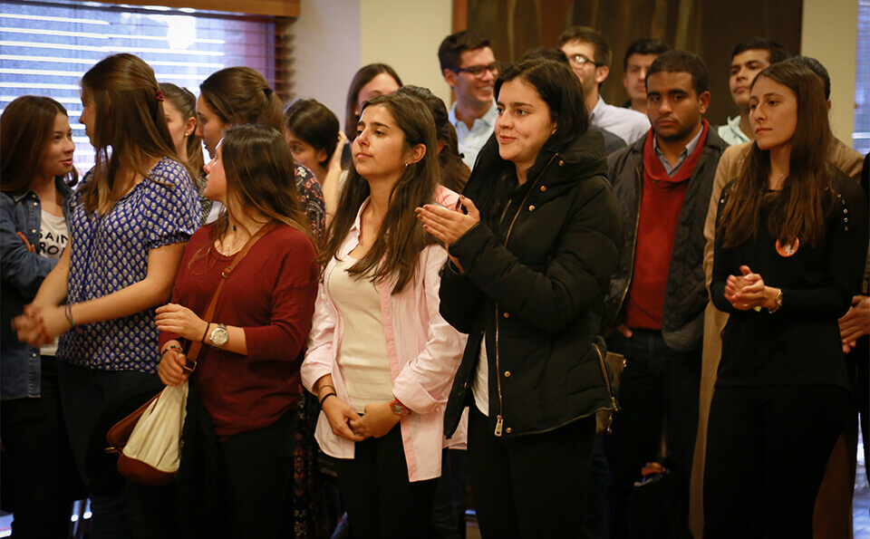 estudiantes en salón aplauden por discurso en ceremonia de donaciones