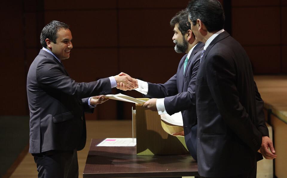 hombre de traje oscuro estrecha la mano con hombre de barba quien le entrega diploma
