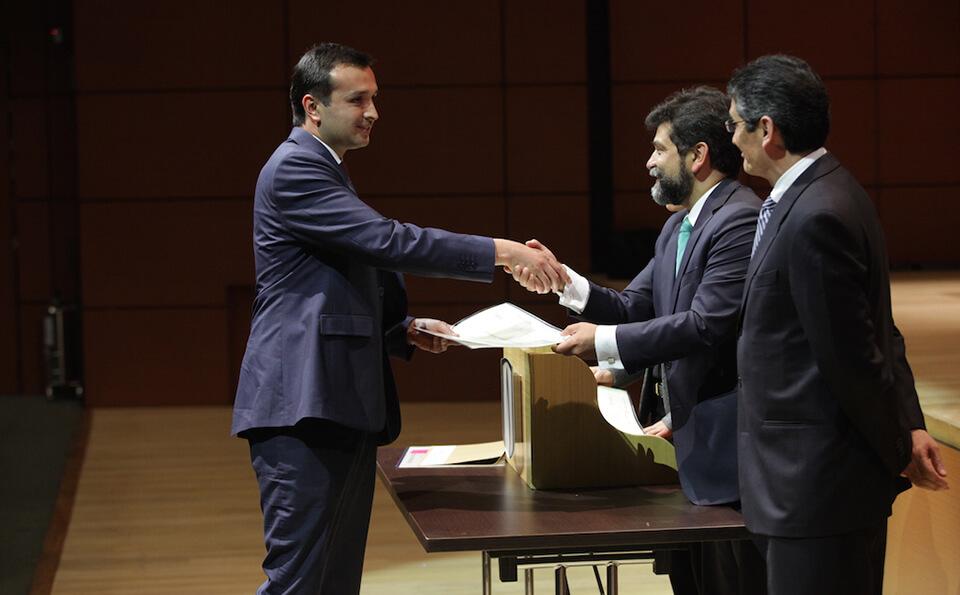 hombre de traje azul estrecha su mano derecha con otro señor mayor y en su mano izquierda recibe diploma de grado