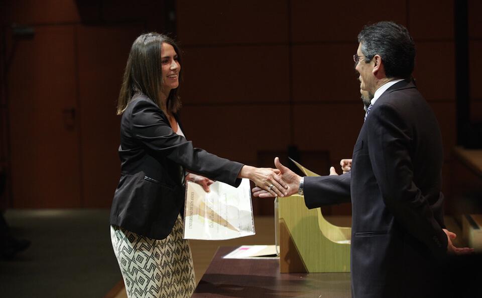 mujer con vestido y chaqueta negra estrecha la mano de un señor en señal de agradecimiento