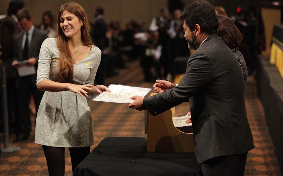 una mujer de vestido gris y cabello rojo recibe diploma