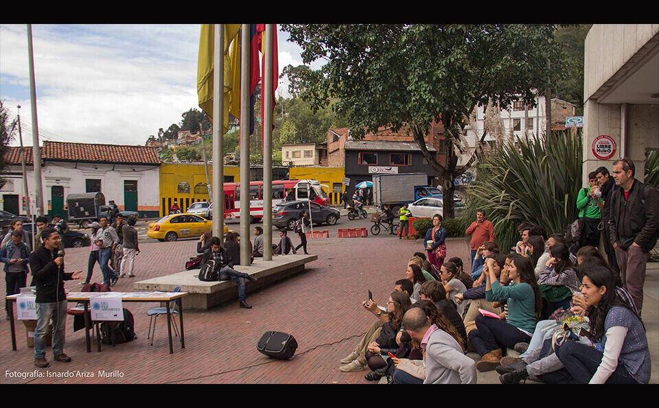 exterior edificio uniandes, estudiantes sentados en el piso en ceremonia de donaciones