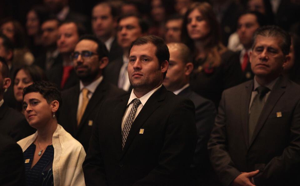 vemos a varias personas de pie en un auditorio en una ceremonia