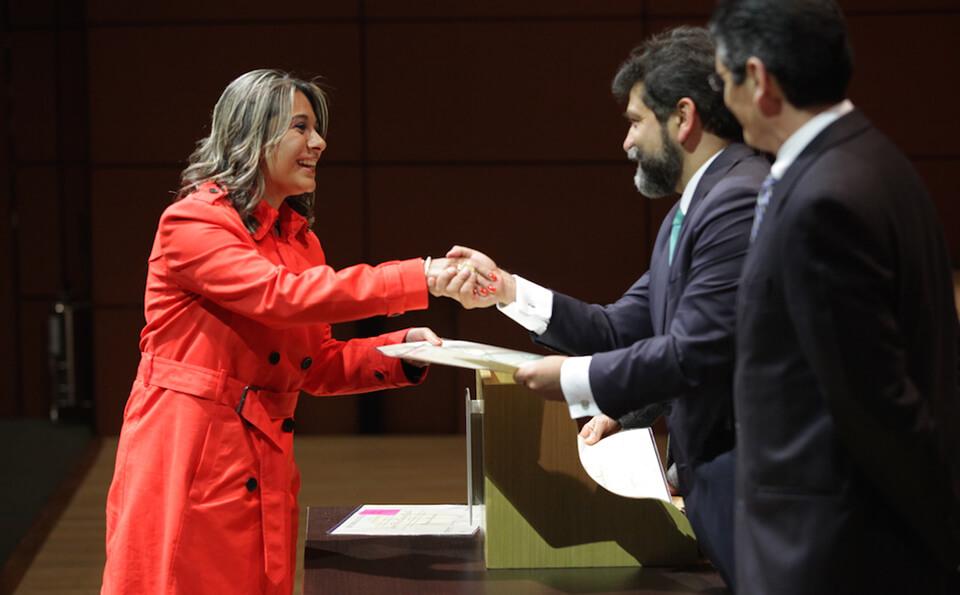 mujer de abrigo color salmón estrecha la mano de un hombre que le entrega diploma