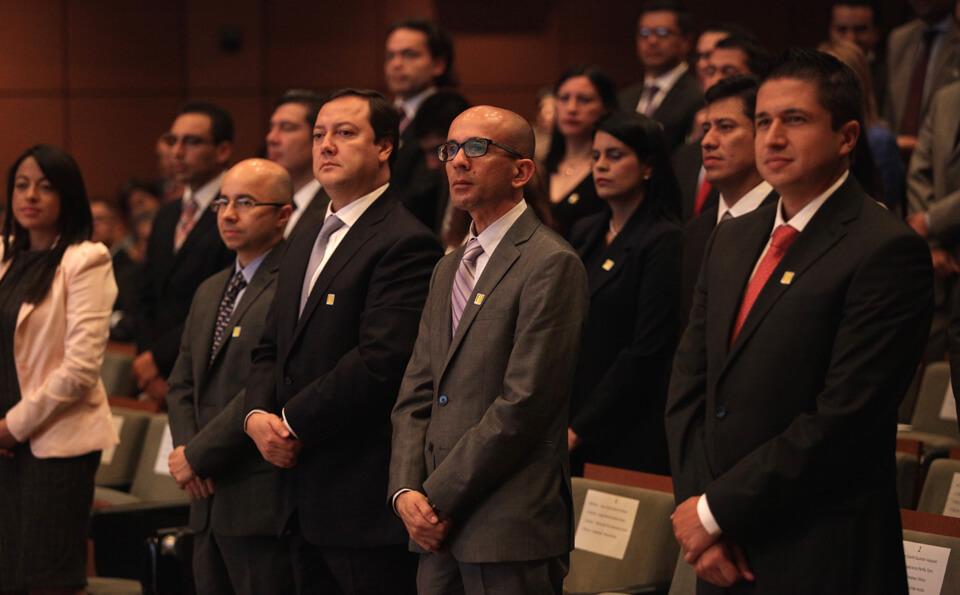 una fila de un auditorio, se ven a las personas de pie esperando a ser llamados