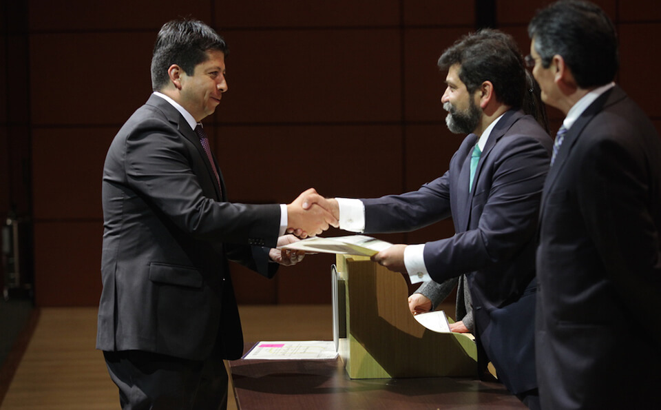 un hombre estrecha la mano de otro hombre al recibirle un diploma de grado