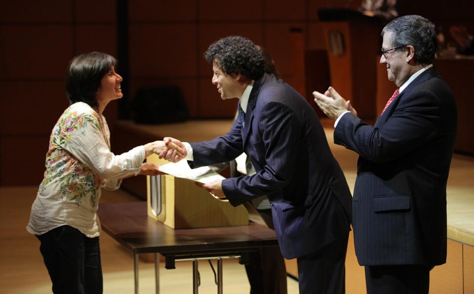 una mujer de pelo corto recibe diploma de un hombre de pelo crespo