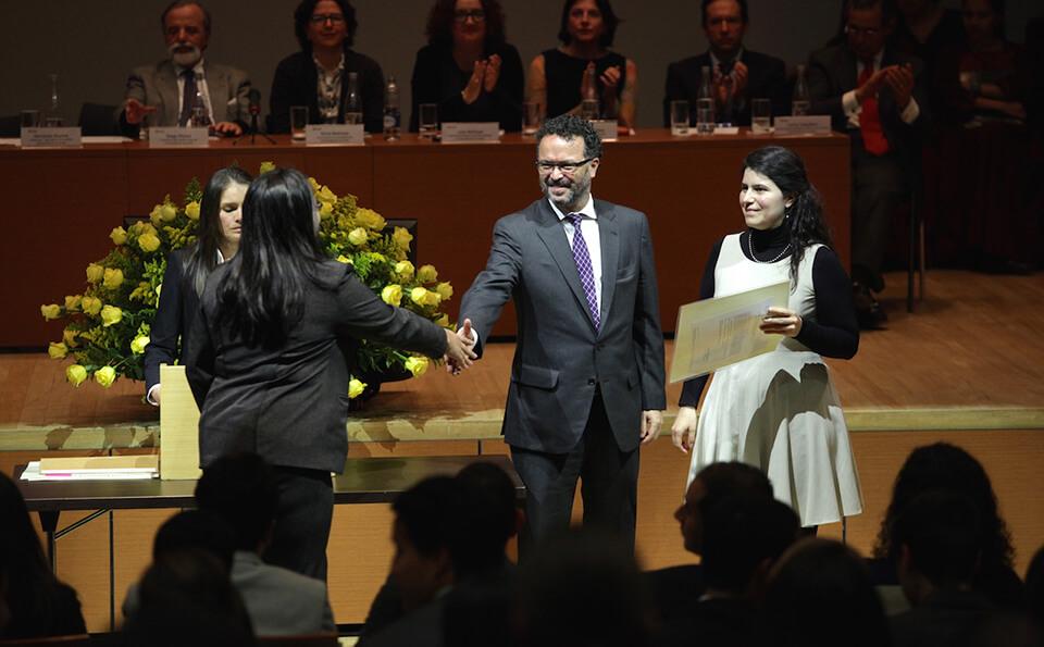 una mujer de ropa negra se acerca a una mesa a recibir diploma de grado