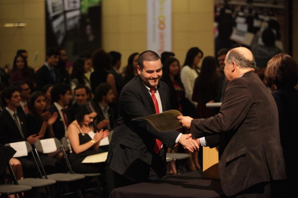joven con corbata roja recibe diploma de grado