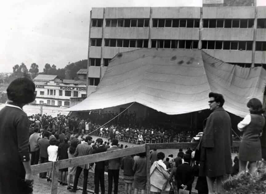 foto antigua en blanco y negro de una ceremonia de grados celebrada al aire libre en la universidad de los andes