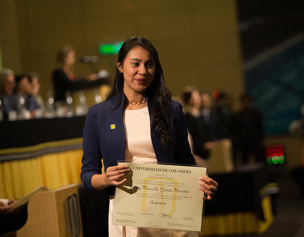 Graduanda de la Universidad de los Andes posa con su diploma de grado